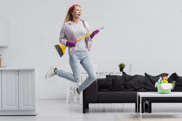 woman jumping while cleaning house
